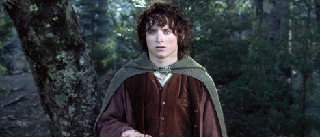 Elijah Wood in The Lord of the Rings. Frodo, wearing a brown coat and green cloak stands along in the middle of a dense green forest. He gazes off-camera, with a look of concern.