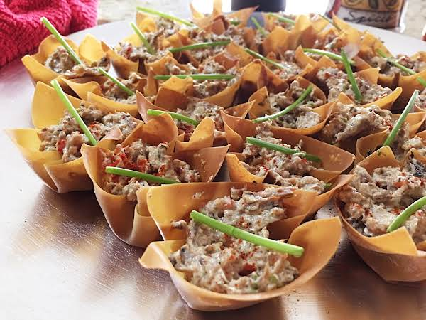 Baked Wonton Wrappers Filled With Sardine Mixture And Garnished With Chives On A Silver Serving Plate.