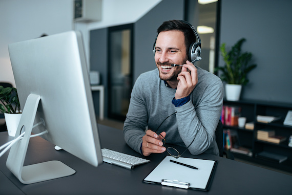 Man with headset laughs while looking at computer