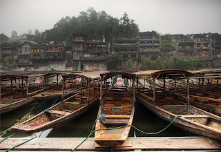 Photo: Boats in Ancient China  This is the ancient village of Feng Huang in distant southern China. I hired a local driver to get me there, and the ride was longer than most plane trips! And a lot less comfortable... Anyway, after arriving, I had a wonderful time exploring. One morning, the old town was covered with thick fog. And it's that still, wet, timeless fog of China. When you are looking at it, you become convinced it will just never go away. I worked my way down one of the banks to an area where the local rivermen keep the boats to grab this shot.   from the blog www.stuckincustoms.com