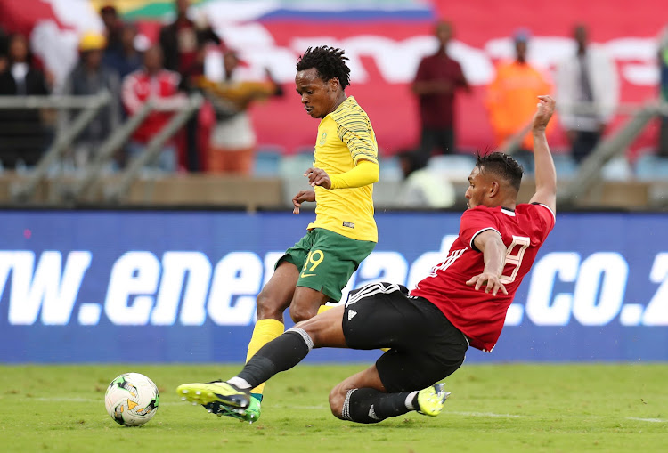SA Belgium-based striker Percy Tau is tackled by Sand Masaud Masaud of Libya during the 2019 Africa Cup of Nations qualifier match between Bafana Bafana and Libya at the Moses Mabhida Stadium in Durban on September 8, 2018.