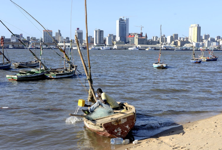 A fisherman cleans his boat beneath Maputo's skyline, Mozambique, August 15 2015. Picture: REUTERS/GRANT LEE NEUENBURG