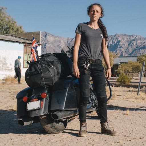 Mulher posando ao lado de uma moto.