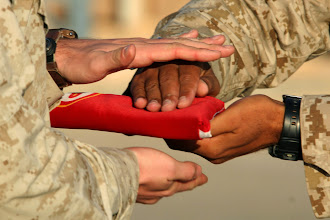 Photo: The Marine Corps flag is passed from one Marine's hands to another's during the transfer of authority ceremony at Al Asad, Iraq, Oct. 7.Photo by: Cpl. James B. Hoke