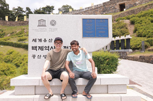 Dnyan and Kyehyun pose together, arm in arm, in front of a monument.
