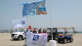 Concejales en la playa de Las Marinas con la bandera de la Q de Calidad.
