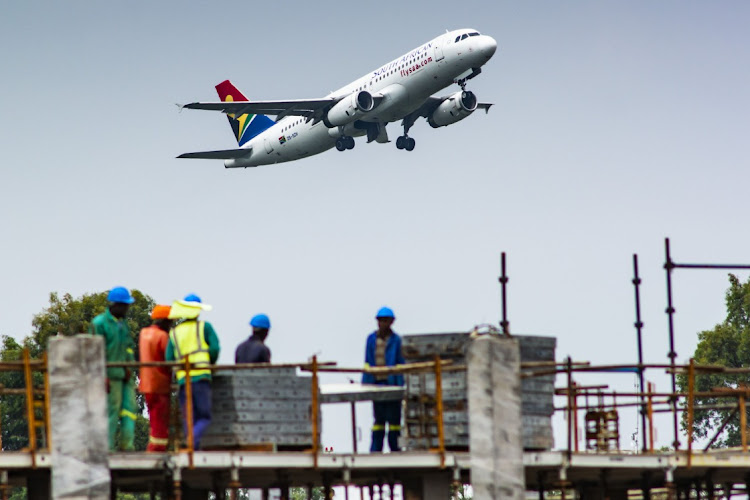 An Airbus A320-200 passenger jet, operated by South African Airlines, flies above a construction site during take-off from OR Tambo International Airport in Johannesburg, in this January 24 2020 file photo. Picture: BLOOMBERG/Waldo Swiegers