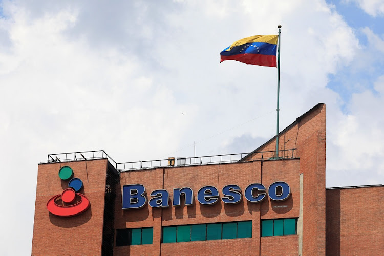 A Venezuelan flag waves above the corporate logo of Banesco bank at one of their office complexes in Caracas, Venezuela, on May 2, 2018. Picture: REUTERS/MARCO BELLO
