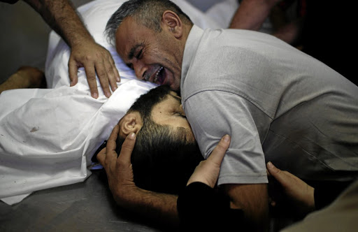 The brother of Palestinian Shaher al-Madhoon, who was killed during a protest at the Israel-Gaza border, reacts over his body at a hospital morgue in the northern Gaza Strip on May 14 2018. Picture: REUTERS