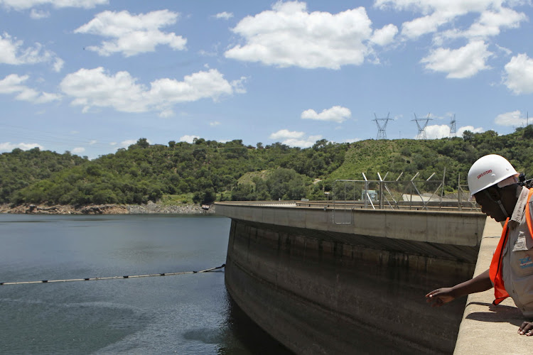 An official of the Zimbabwe Electricity Supply Authority inspects water levels on the Kariba Dam in Zimbabwe. File photo