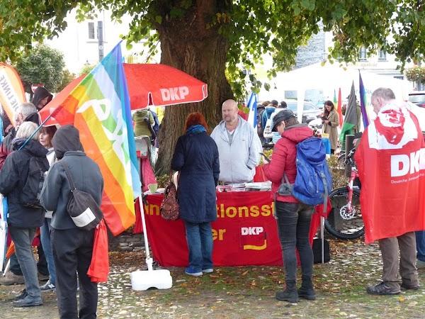 DKP-Infostand mit Schirm, Demonstrierende mit Fahnen.