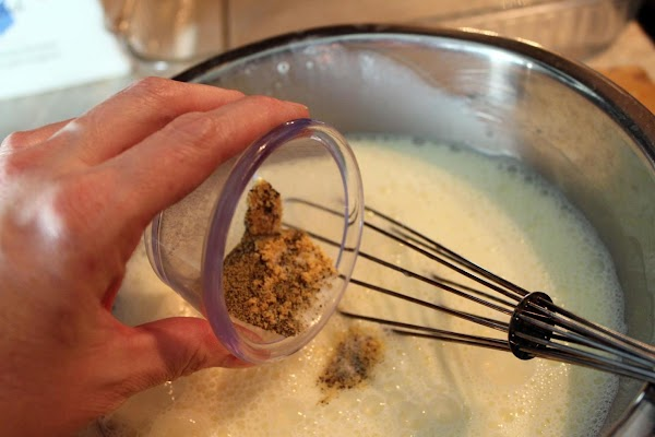 Dry mustard added to whisked eggs and milk in a bowl.