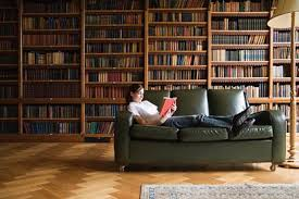 Woman comfortably reading in a well-stocked library while lounging on a leather sofa