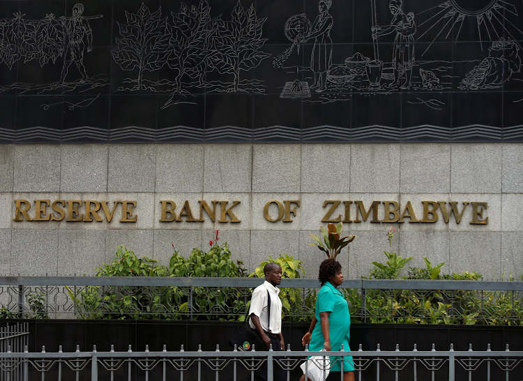 People walk past the Reserve Bank of Zimbabwe building in Harare, Zimbabwe, February 25 2019.