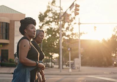 The founders, Ashlee Ammons and Kerry Schrader, walk along a street at sunset.