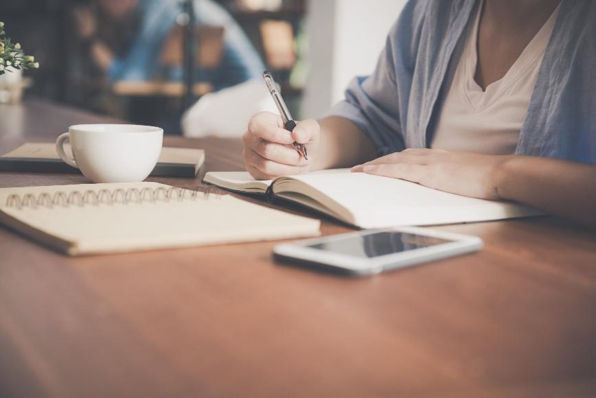 Wanita Menulis Di Buku Catatan Di Samping Cangkir Teh Dan Komputer Tablet