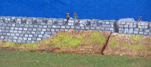 Photo: Le mura della città. Si nota il terrapieno ancora incompleto.Miniature Baccus, materiale scenico autocostruito.