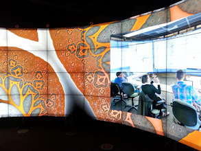 """Photo: Fractal backdrop for primary image of financial analysts and planners using the CAVE2 facility.  Remininscent of the accountants' landscape in Douglas Adams, 'Mostly Harmless': """"It was a universe of densely enfolded worlds, of wild topographies, towering mountain peaks, heart-stopping ravines, of moons shattering off into seahorses, hurtful blurting crevices, silently heaving oceans and bottomless hurtling hooping funts... So this was where accountants spent their time. There was clearly more to them than met the eye. [Ford Prefect] looked around carefully, trying not to let it all swell and swim and overwhelm him.""""  Imagery courtesy of UIC EVL, CALIT2 UCSD, Australian Synchrotron, KAUST, and Monash University"""