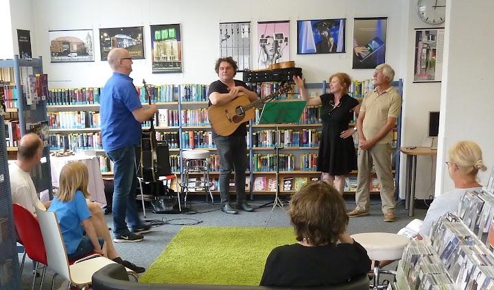 Bibliotheksleiterin Marion Meier-Esser im angeregten Gespräch mit Werner Burkard und dem Musiker Michael Lembach mit Gitarre.