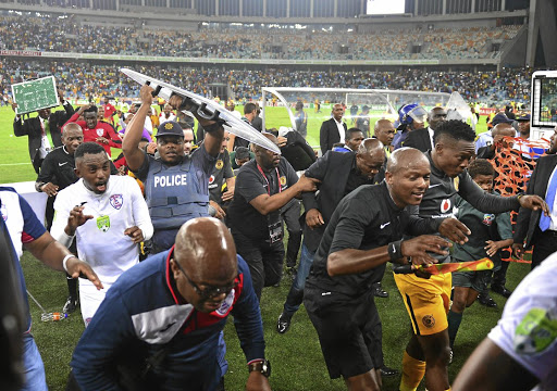 Mayhem: Former Kaizer Chiefs coach Steve Komphela (in black jacket and jeans) runs for cover with match officials, players and police after his team was knocked out of the Nedbank Cup by Free State Stars on Saturday night. He quit soon afterwards. Picture: SAMUEL SHIVAMBU/ BACKPAGEPIX