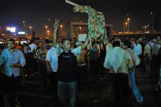 Photo: A man carries an effigy of an army officer...