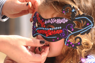 Photo: Carmela Rogers of Swansboro has her Mardi Gras mask adjusted before the parade on Saturday. (Dylan Ray photo)