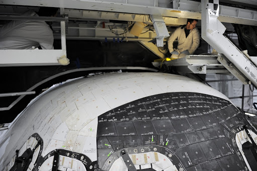 Inside Orbiter technicians prepare space shuttle Atlantis for removal of the top emergency escape window.