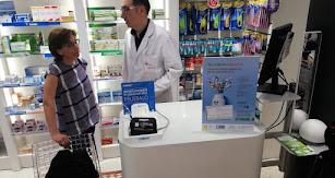 Un farmacéutico atiende a una usuaria.