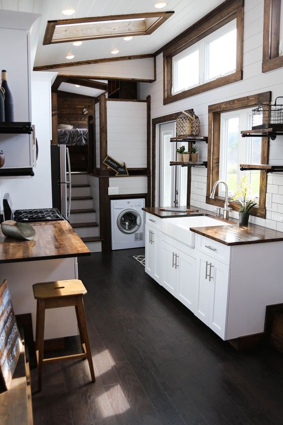 brown and white tiny home interior with white shaker kitchen cabinets, dark wood floors, built in laundry, and a large apron front sink - tiny house kitchen layout, tiny house like hgtv tiny homes, tiny kitchen design