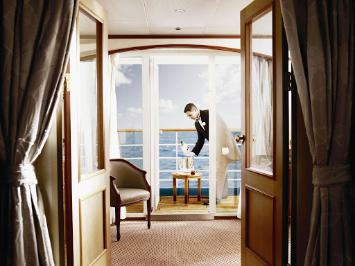 A butler on a Silversea sailing pours champagne on a guest's veranda.