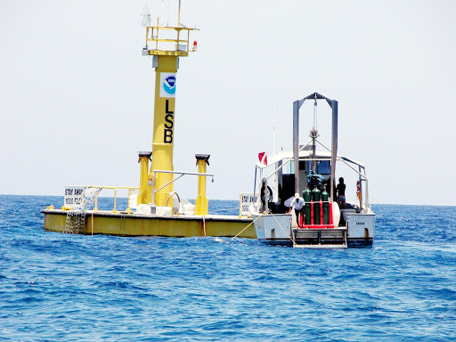 A dive boat is moored to the Life Support Buoy anchored above the station Aquarius offshore from Key Largo.
