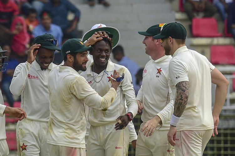 Zimbabwe cricketer Sikandar Raza (2nd L) congratulates teammate Brandon Mavuta (C) after the dismissal of the Bangladesh cricketer Nazmul Hossain Shanto during the fourth day of the first Test cricket match between Bangladesh and Zimbabwe in Sylhet on November 6, 2018.