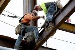 Notice the harnesses attached to the ironworkers. Read about their work: https://www.dailyastorian.com/news/northwest/iron-workers-brave-perils-while-building-new-portland-tower/article_b0d92241-0c7f-53ce-8be4-a8f17025c91c.html