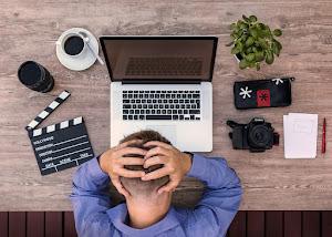 fotograaf met hoofd tussen de handen voor een computer met film klapbord, fototoestel, kladblok, koffie enz.