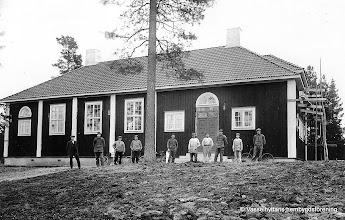 Photo: Byggnaden uppfördes nästan helt ideellt av ortens egen befolkning. Timret kom från skogarna omkring Vasselhyttan och en del från Ramsbergs Bruk. Erik Bohman fraktade dit virket med häst. Snickerifirman Ferdinand Fransson i Storå levererade Bygdegårdens bänkar och stenhuggerifirman Karl Sandberg i Kopparberg levererade granittrappen. Gustaf Persson från byn, fungerade som arbetsledare. Innan Bygdegården fanns, hade byborna haft sina sammankomster i den gamla skolan. Efter två års arbete kunde Bygdegården invigas till julen 1922.