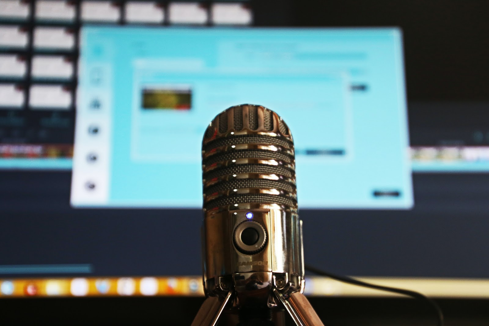 Microphone in front of a computer screen ready to record a podcast for a startup business.