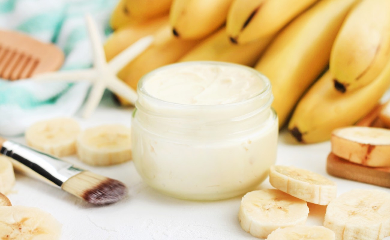Jar of white lotion surrounded by bananas to imply natural skincare