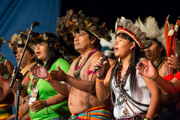 A group of Surui men and women sing.
