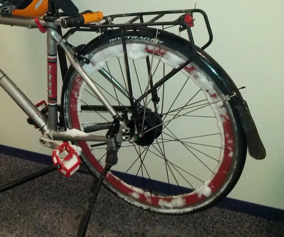 A bike wheel full of snow