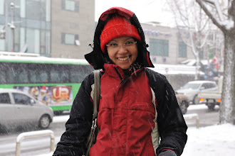 Photo: When we finished our visit to Leeum, Samsung Museum of Art, the snowing intensified causing chaos on the street. The road was slippery. To take this picture, first I needed to find a shelter to hide (water is bad for camera!) Next, Cynthia needed to get out into the snow, pose, and smile while waiting for me to work my magic with the camera.