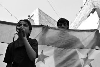 Photo: A young boy leads chants at an anti-government protest in the neighbourhood of Bustan Kasr in Aleppo, Syria. Anti-government demonstrations typically take place across the city each Friday. Aleppo, SYRIA - 26/4/2013. Credit: Ali Mustafa/SIPA Press