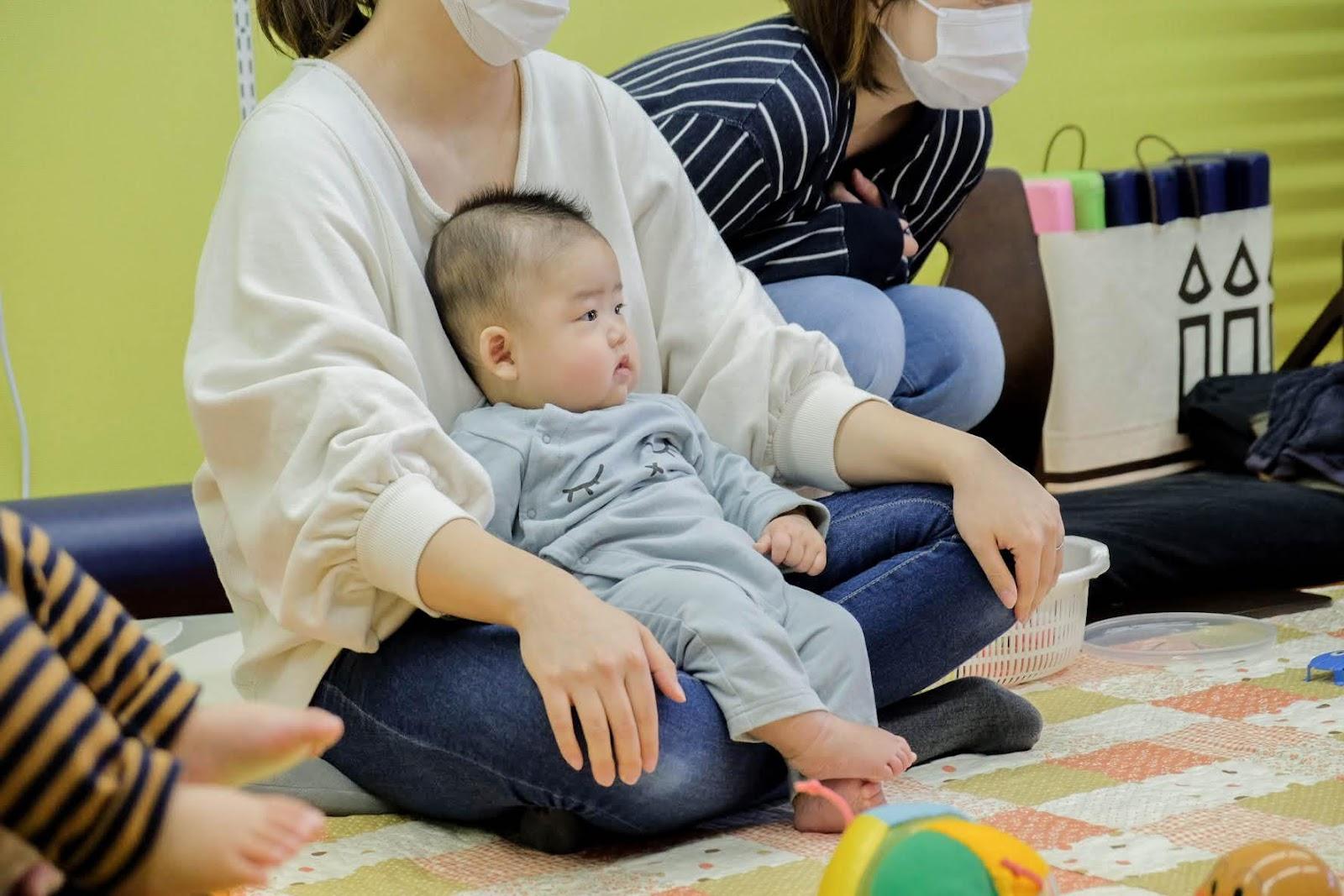 赤ちゃんを抱いて寝ている子供  中程度の精度で自動的に生成された説明