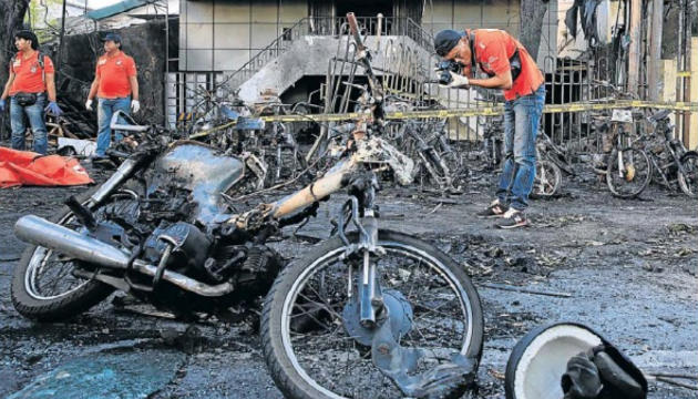 A forensic police officer takes pictures of debris near burned out motorcycles following a blast at the Pentecost Church Central Surabaya in Indonesia