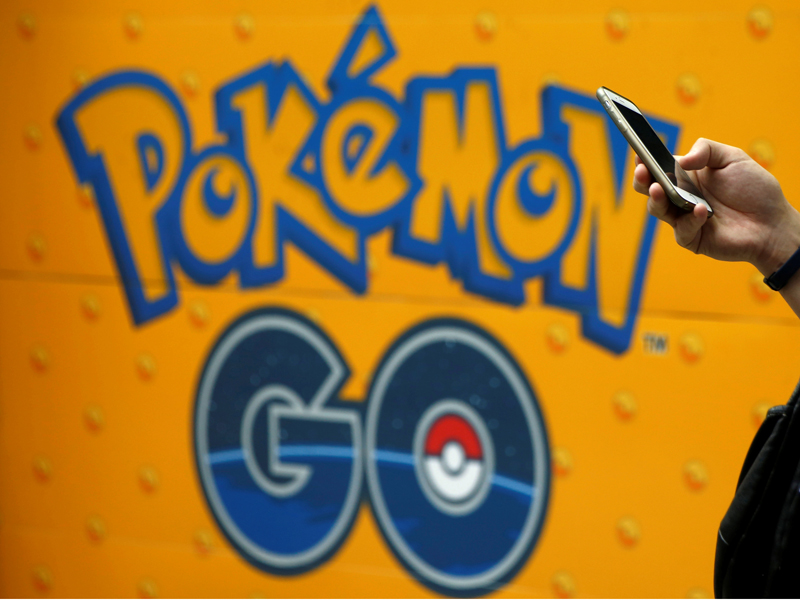 "A man uses a mobile phone in front of an advertisement board bearing the image of ""Pokemon Go"" at an electronic shop in Tokyo on July 27, 2016. Photo courtesy of REUTERS/Kim Kyung-Hoon/File Photo*Editors: This photo may only be republished with RNS-POKEMON-BISHOP, originally transmitted on Aug. 18, 2016."