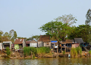 Photo: Many people live along the river.  Since the river rises during the rainy season, dwellings are built on stilts.