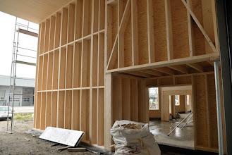 Photo: 12-11-2012 © ervanofoto In de doorgang naar het magazijn is de stelling verwijderd. Hierdoor hebben we een goed zicht op de mooie structuur van het houtskelet. Van hieruit is er ook een mooi doorzicht via het buitensas, de showroom en de hoofdingang tot in de burelen. Helaas zal dit zicht niet lang ongeschonden blijven. Zodra de wanden geisoleerd en dichtgelegd zullen worden verdwijnt deze mooie houten structuur definitief. Dus, nog snel even genieten van het mooie zicht op dit prachtige natuurlijke materiaal.