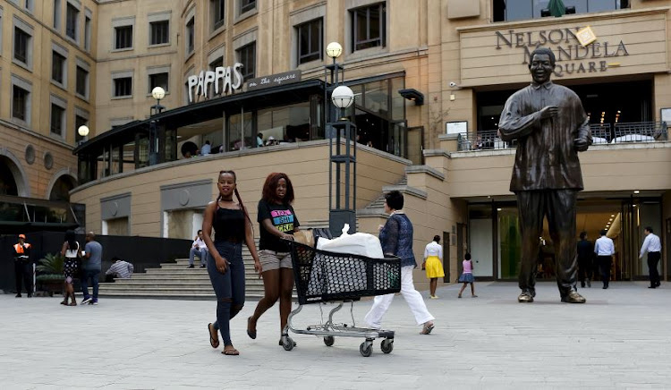 Shoppers push trolleys at an upmarket shopping mall in Sandton. The retail sector did better than expected in August.