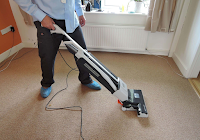 A man vacuuming a carpet from the side