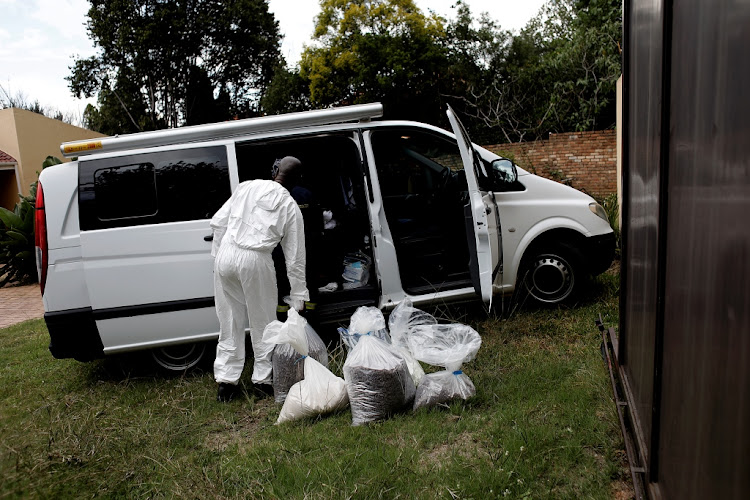 A police forensics officer loads drugs into a van following a major drug bust at a home in Sandton, Johannesburg, on Thursday March 28 2019.