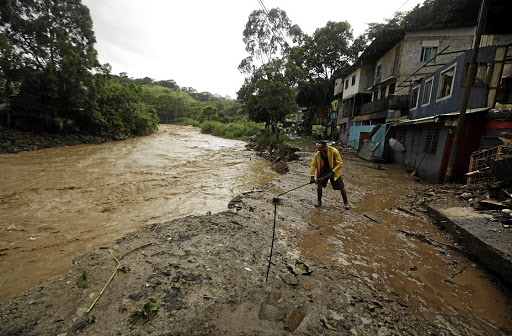 A man cleans a street flooded by the Tiribi River during heavy rains brought by tropical storm Nate, in San Jose, Costa Rica, on October 5 2017. Picture: REUTERS